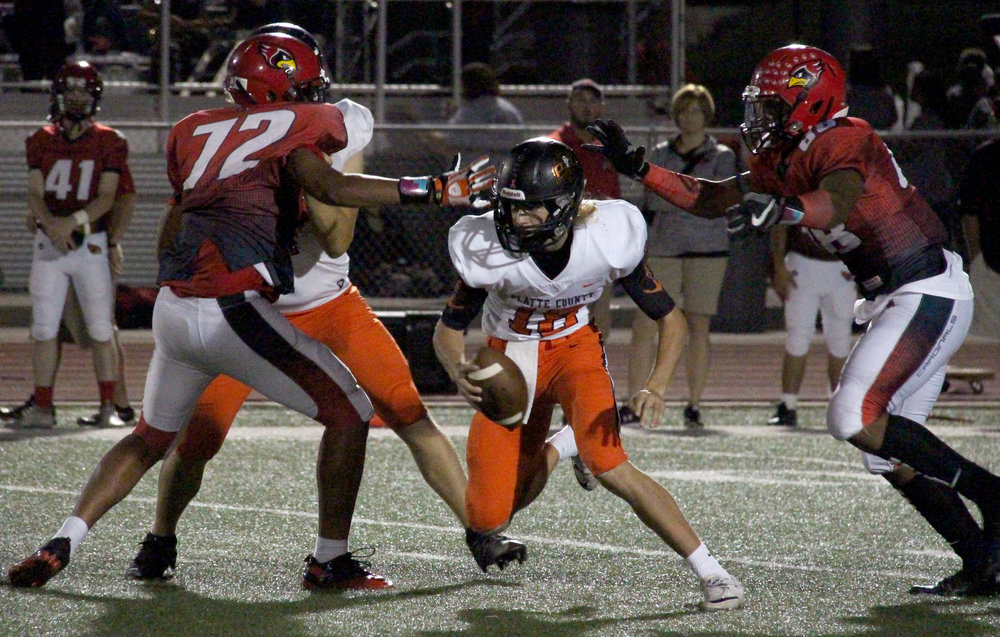 ROSS MARTIN/Citizen photo Platte County senior quarterback Tanner Clarkson, center, looks for room to run between Raytown South defenders Friday, Sept. 29 in Raytown, Mo.