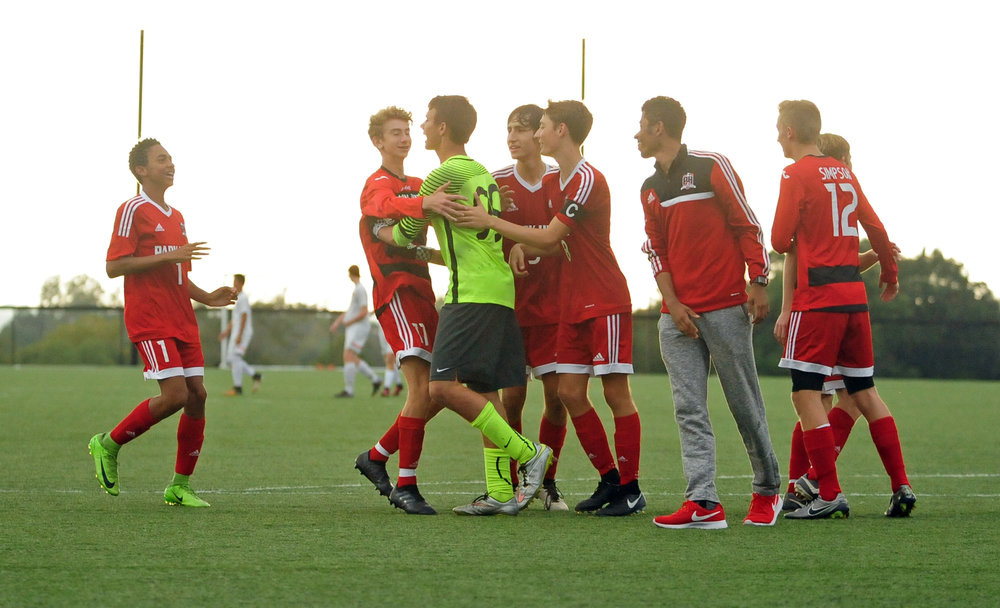 NICK INGRAM/Citizen photo Park Hill players celebrate with goalkeeper Gabe Smith (99) after the Trojans beat Platte County in the Panther Classic on a penalty kick shootout Thursday, Oct. 5 at Park Hill District Soccer Complex in Riverside, Mo.