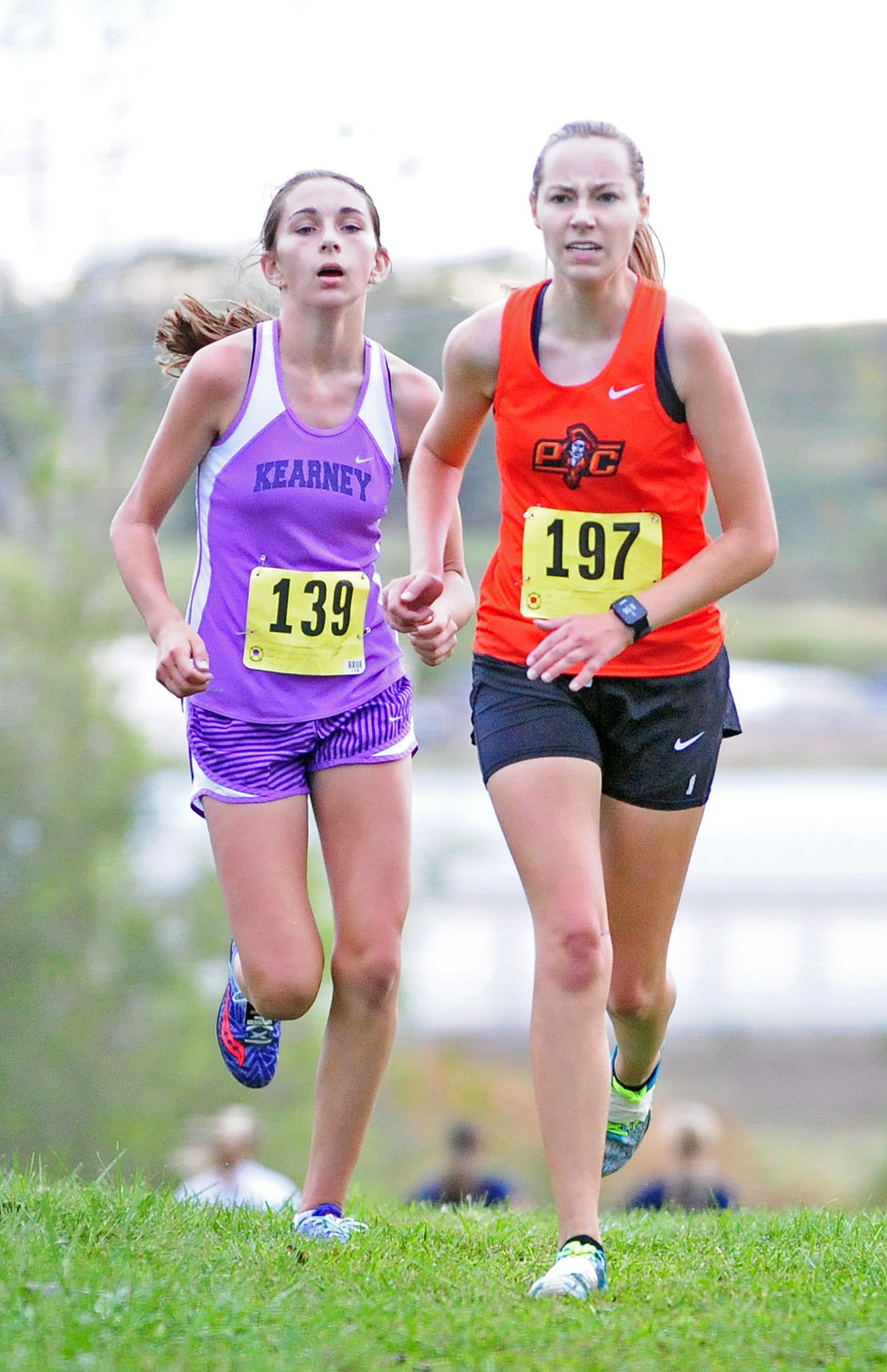 NICK INGRAM/Citizen photo Platte County senior Lauren Johnson (197) battles with a Kearney runner near the finish line of the Suburban Conference Blue Division Championships on Saturday, Oct. 7 at Jesse James Fairgrounds in Kearney, Mo.
