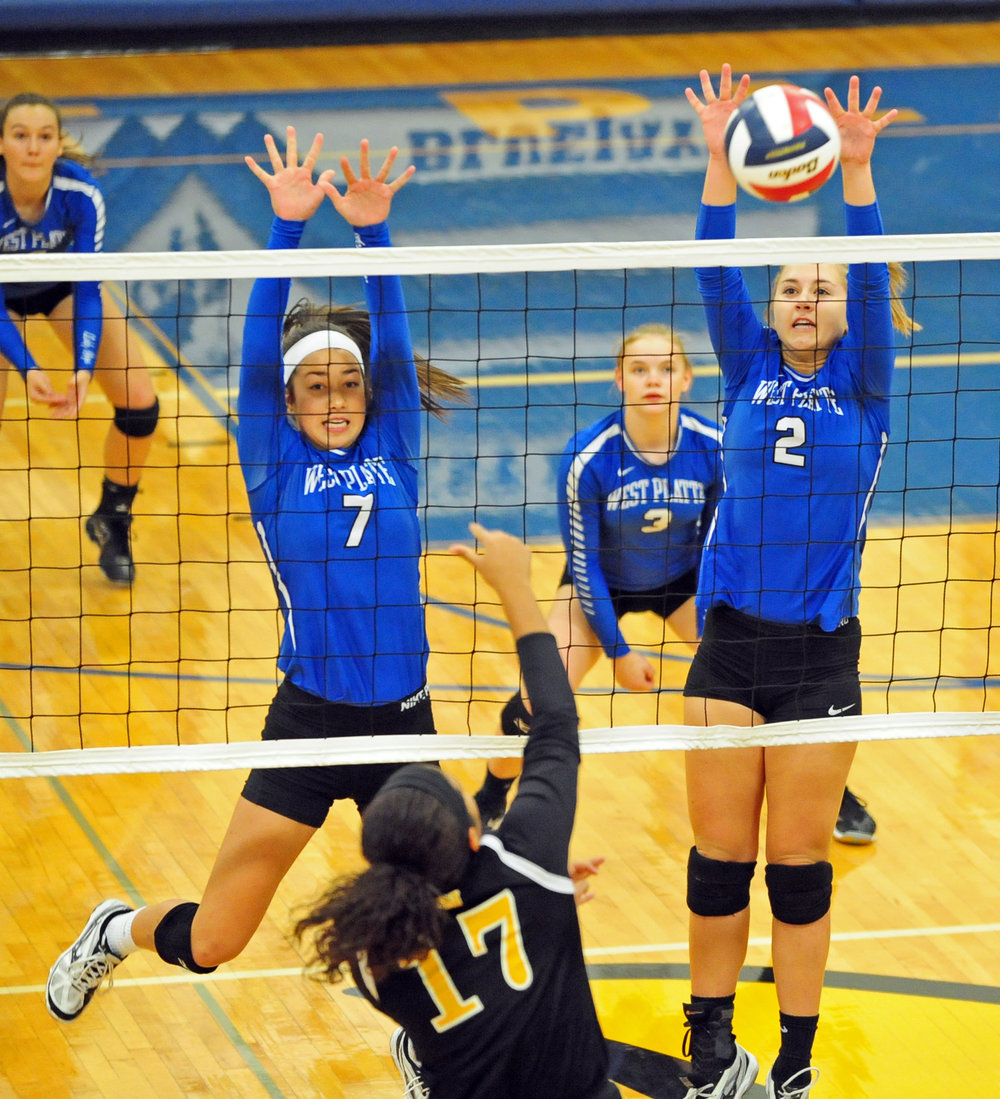 NICK INGRAM/Citizen photo West Platte junior Tori Norman, left, and sophomore Sam Rotterman, right, go up for a block against Wellington-Napoleon on Monday, Oct. 16.