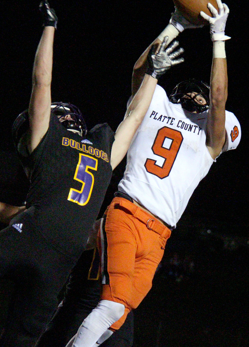ROSS MARTIN/Citizen photo Platte County junior wide receiver Dylan Gilbert, right, makes a catch over a Kearney defender on Friday, Oct. 13 in Kearney, Mo.