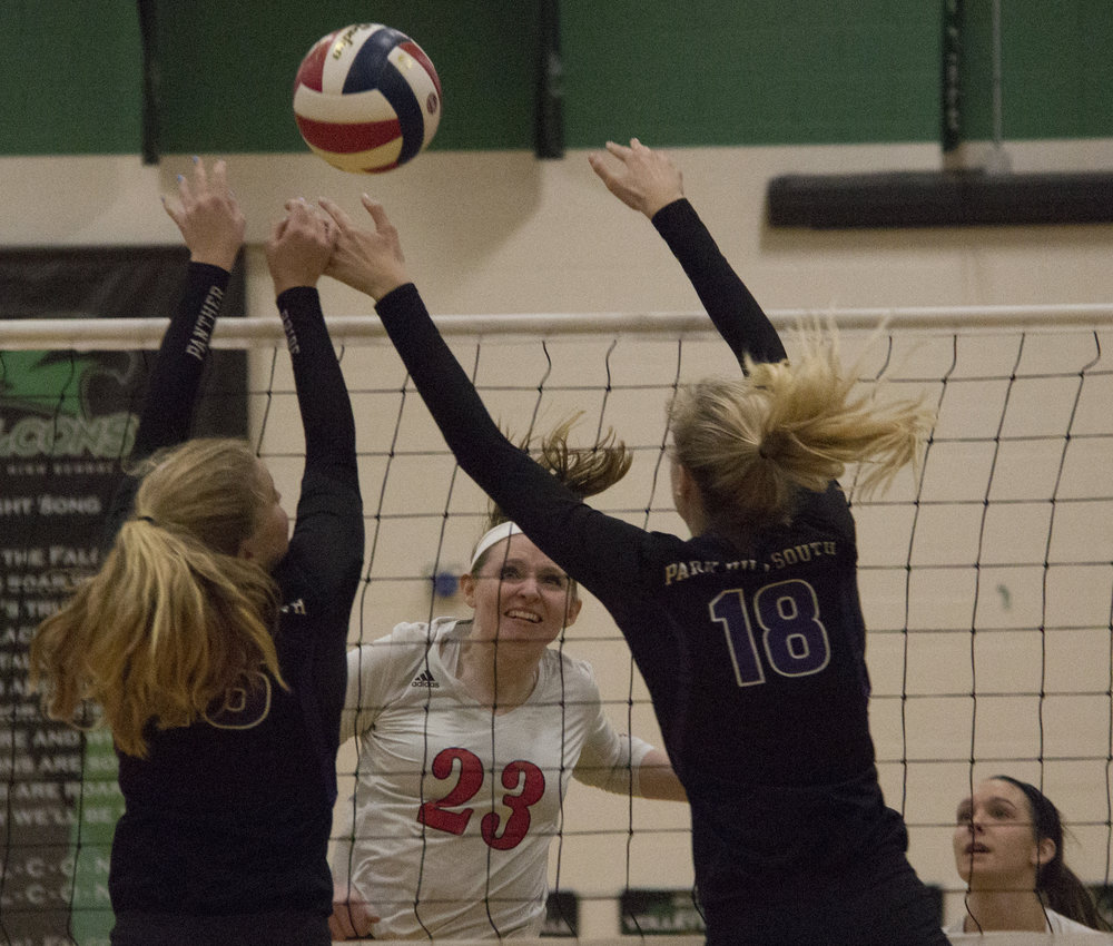 ROSS MARTIN/Citizen photo Park Hill senior Kai Welsh, center, watches her spike go through the defense of Park Hill South's Abbie Day, left, and Annika Welty during the Class 4 District 16 championship match Wednesday, Oct. 18.