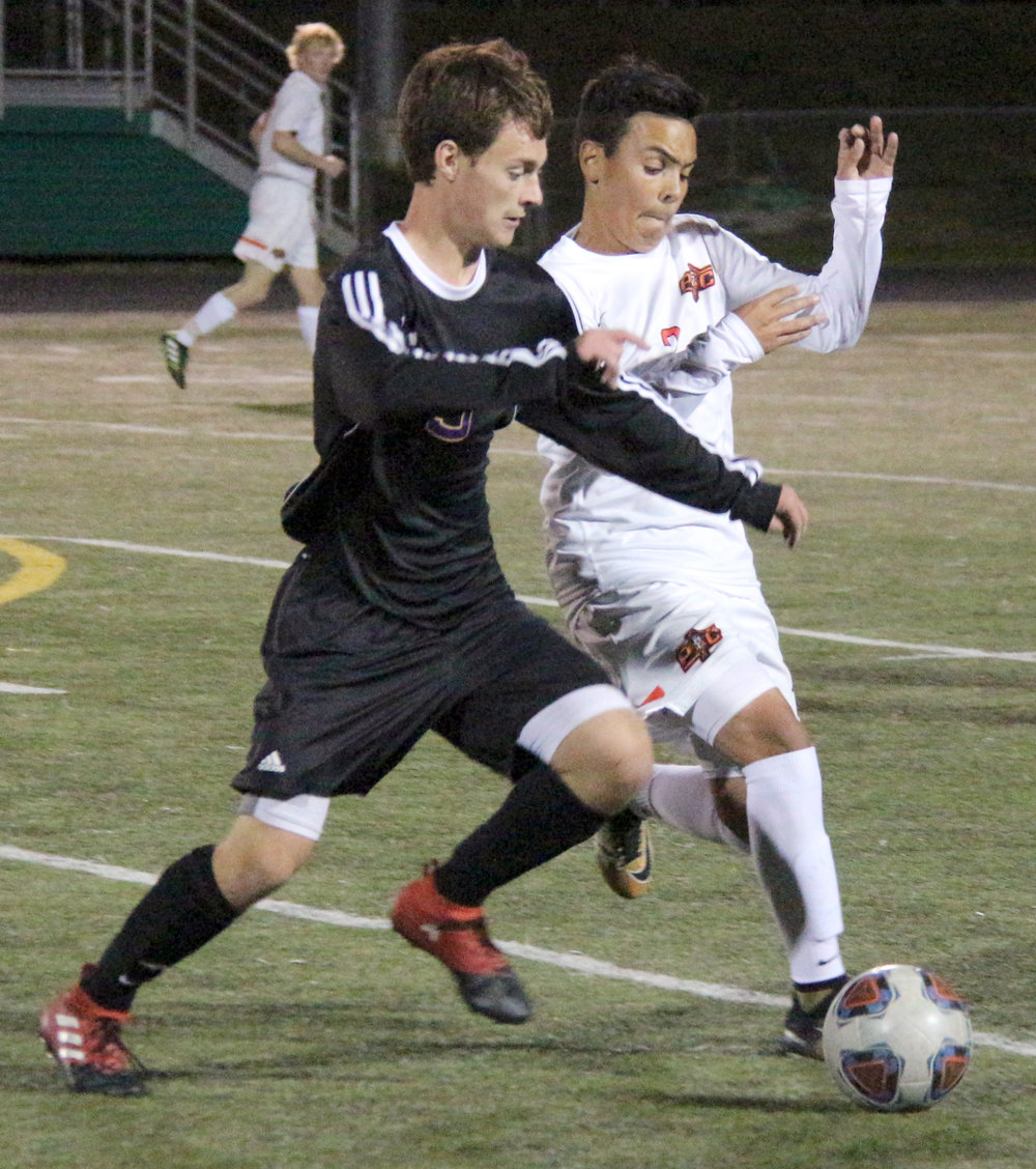 ROSS MARTIN/Citizen photo Platte County sophomore midfielder Chase Peterson (right) battles for a loose ball with a Kearney defender during a Class 3 District 16 semifinal Monday, Oct. 23 at Smithville High School in Smithville, Mo.