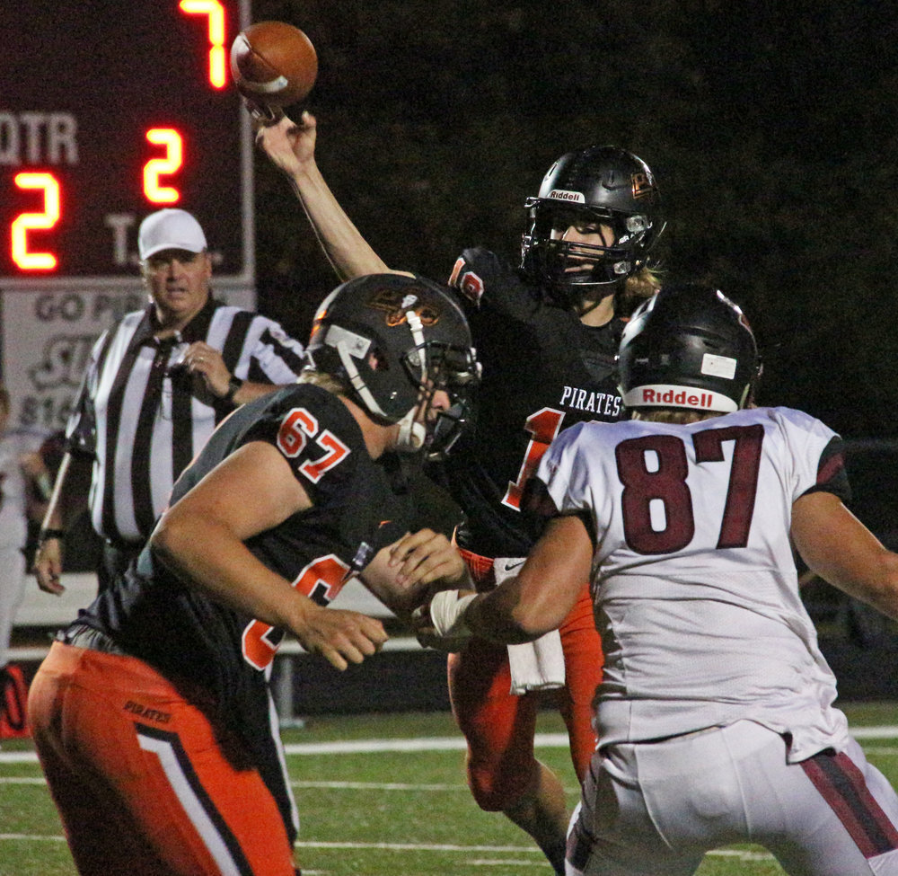 ROSS MARTIN/Citizen photo Platte County quarterback Tanner Clarkson throws a pass behind blocking from senior guard Matthew Knopp against Benton on Friday, Oct. 20 at Pirate Stadium.
