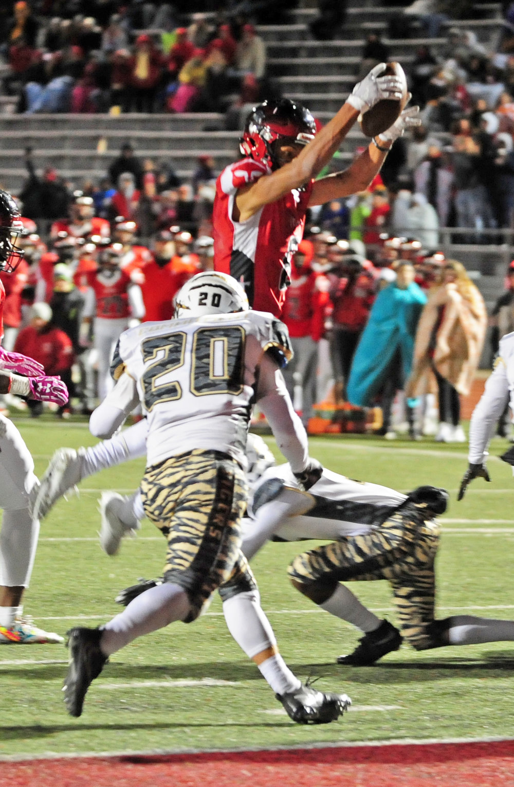 NICK INGRAM/Citizen photo Park Hill senior wide receiver Ronnie Bell, right, leaps toward a Lee's Summit defender on his way into the end zone during a Class 6 District 4 semifinal Friday, Oct. 27 at Park Hill Disrict Stadium in Kansas City, Mo.