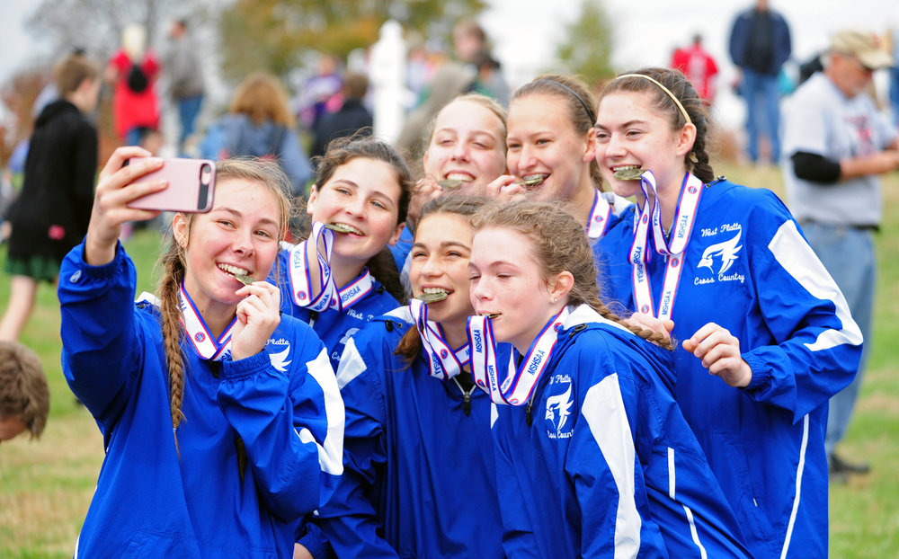 NICK INGRAM/Citizen photo West Platte senior Rachel Heili, left, takes a selfie with teammates juniors Lea Moose and Lindsay Goodwin, sophomore Lexi Elmore and freshmen Sophia Rush, Katy Tharp and Bella Clark after winning the Class 1 Missouri State Cross Country Championships team title Saturday, Nov. 4 at Oak Hills Golf Center in Jefferson City, Mo.