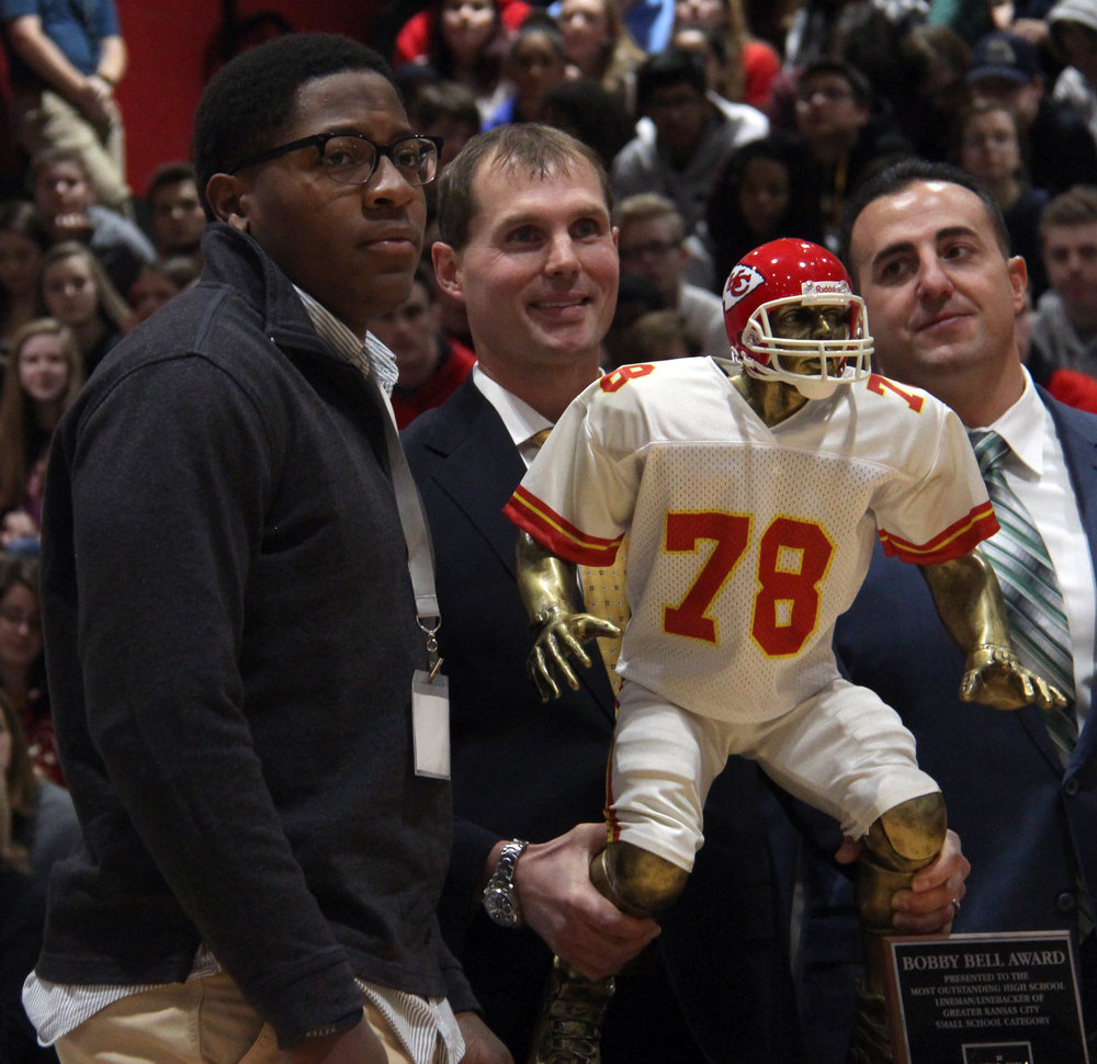 ROSS MARTIN/Citizen photo Platte County senior defensive end Michael Smith, left, won the Bobby Bell Award during a ceremony Tuesday, Dec. 5 at Park Hill High School in Kansas City, Mo. He received the trophy — given to the top lineman/linebacker from a small school in the Kansas City metro area — from the award's inaugural winner and 2001 Platte County graduate Brian Koechner, center.