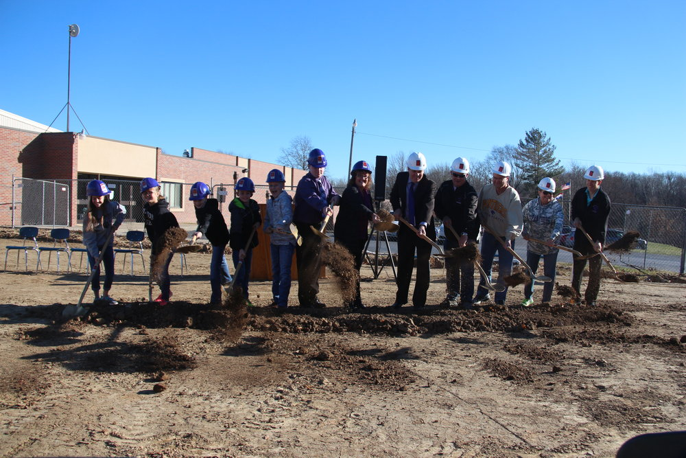 ROSS MARTIN/Citizen photo From left, North Platte students Bella Kitmitto, Courtney Dehn, Landon Bartlett, Noah Heckman and Clayton Rotterman; officials Riley Hyde, Michelle Johnson, Karl Matt, Mark Fisher, Eric Meadows, Carla Shanks and Mark Heckman pitch away some ceremonial dirt during a groundbreaking Friday, Dec. 1 at the site of the new junior high building in Dearborn, Mo. Construction on the $5.4 million project is slated to begin this week.