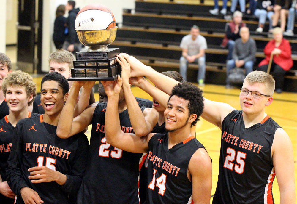 ROSS MARTIN/Citizen photo Platte County players, from left, Nathen Mair, Deiondre Ragsdale, Kobe Cummings and Lucas Stanley celebrate with the Savannah Invitational trophy after beating Chillicothe in the championship game Saturday, Dec. 2 in Savannah, Mo.