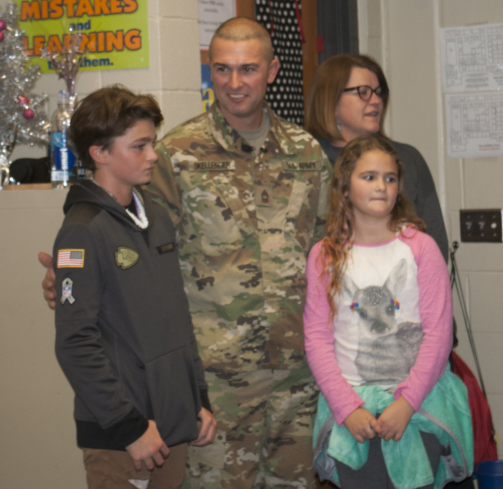 JEANETTE BROWNING FAUBION/Citizen photo U.S. Army Master Sgt. Scott Skellenger surprised his son Gavin (left) and daughter Chloe (right) with an early return from deployment in Kuwait at their schools on Friday, Dec. 8. The family was reunited in this photo at Plaza Middle School, where Gavin attends sixth grade. Another surprise reunion was held earlier in the day at Union Chapel Elementary School, where Chloe attends fourth grade.