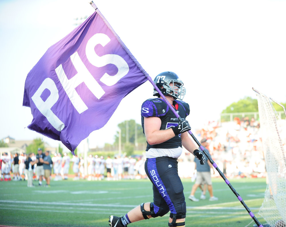 Citizen file photo Park Hill South senior Ben Becker carries the team flag onto the field ahead of a game against Park Hill earlier this season.