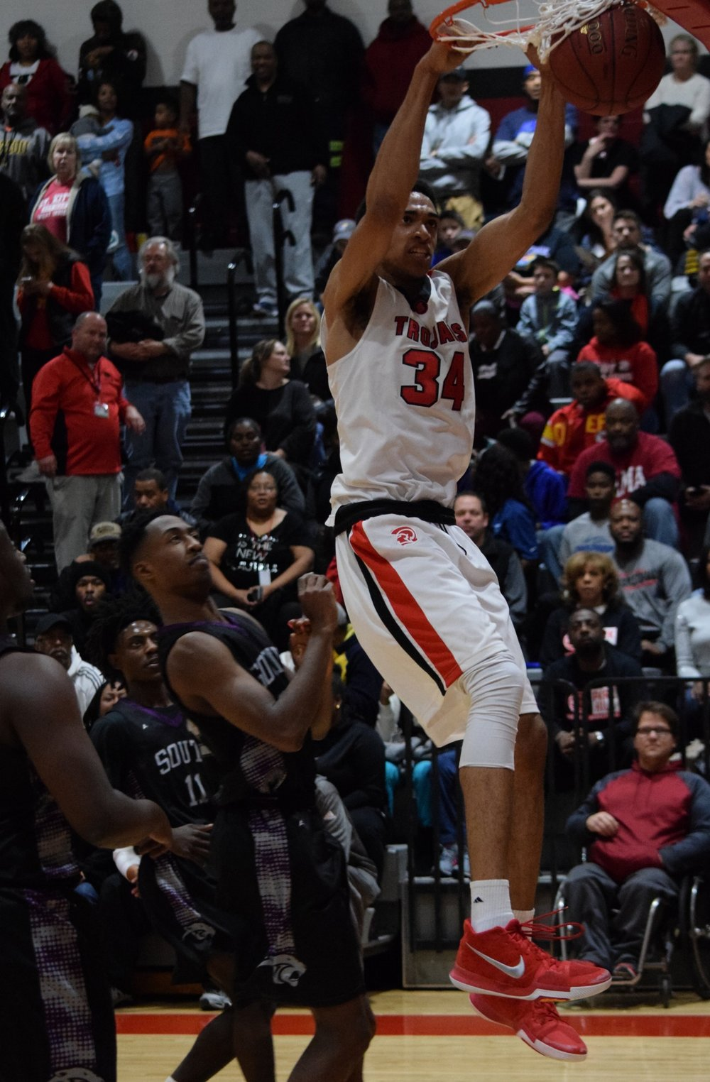 BRYCE MERENESS/Special to The Citizen  Park Hill senior forward Cecil Lee (34) finishes a dunk against Park Hill South on Wednesday, Dec. 20 at Park Hill High School in Kansas City, Mo.