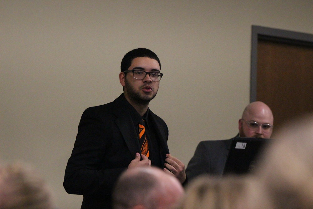 CODY THORN/Citizen photo Platte County senior Joel Rodriguez, who used technology provided by the district to design the school's logo on wood that is now on display in the Board of Education meeting room, discusses the project that he started this year. His artwork was unveiled during the meeting on Thursday, Jan. 18.