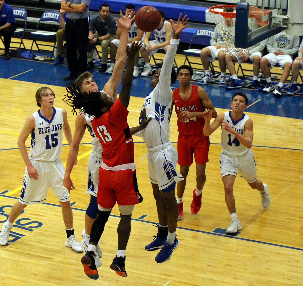 CODY THORN/Citizen photo Park Hill senior Willie Majok attempts a shot over a block attempt in the semifinals of the  C.W. Stessman Invitational at Liberty High School. The Trojans won the tournament with a 58-39 win over Lee's Summit West.