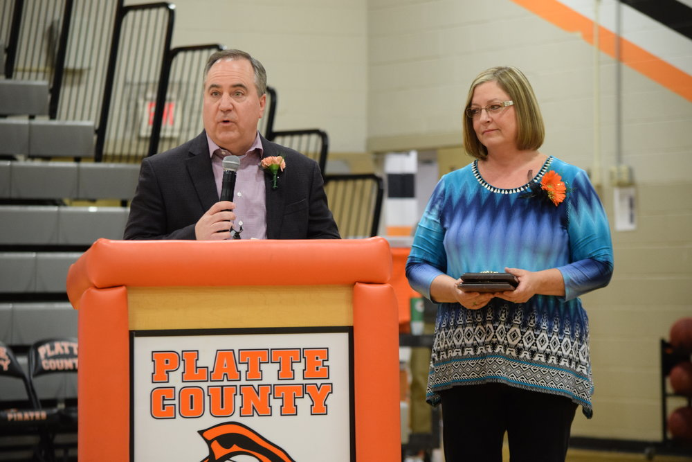 BRYCE MERENESS/Citizen photo Robert Barmann, left, talks to the crowd after he and his wife, Camelia, right, were inducted into the Platte County Pirates Hall of Fame. The Barmanns have three children graduate from PCHS and their youngest, Janessa, is a student at the high school.