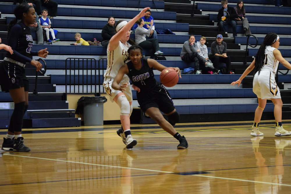 BRYCE MERENESS/Citizen photo Park Hill South's DeQuaria Guillory, center, dribbles around the defense of a Liberty North defender during a game on Monday, Feb. 5, at Liberty North High School in Liberty, Mo. Park Hill South won the game 47-37.