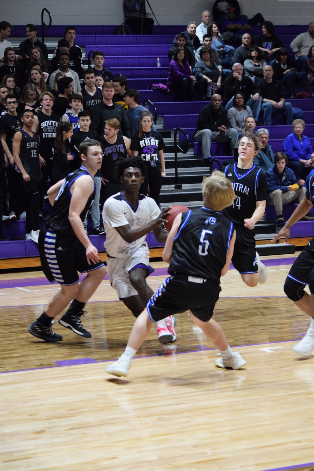 BRYCE MERENESS/Citizen photo Park Hill South junior Lamell Robinson, center, looks for a driving lane in the Panthers 63-48 win against St. Joseph Central on Friday, Feb. 16 at Park Hill South High School.