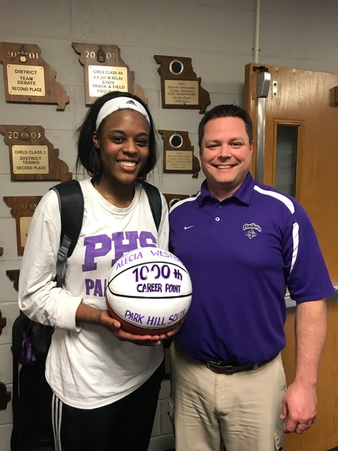 Contributed photo Park Hill South's Alecia Westbrook, left, was presented with a commemorative basketball by coach Josh Dorr (right) after scoring her 1,000th point recently.