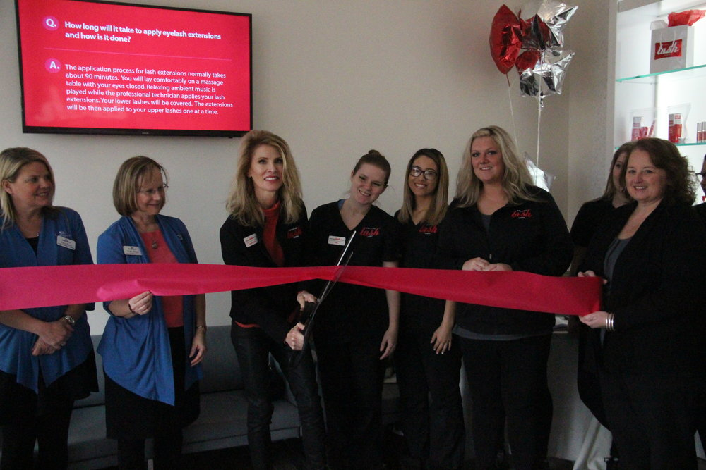 CODY THORN/Citizen photo Sandra Green (center) uses a pair of scissors to cut a red ribbon during a ceremony held by the Parkville Chamber of Commerce on Thursday, Feb. 15, at her business Amazing Lash Studio in the Zona Rosa shopping center in Kansas City, Mo.