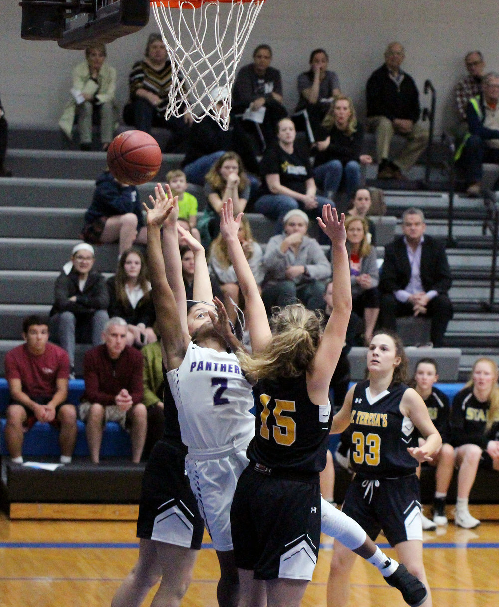 CODY THORN/Citizen photo Park Hill South guard Dymeria Guillory (2) goes up for a basket between two St. Teresa's Academy defenders, including Clare Herrington (15) during the Class 5 District 14 semifinal game on Wednesday, Feb. 28 at Rockhurst High School in Kansas City.