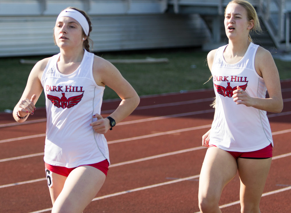 Special to the Citizen/KCPrepReport.com Mackenze Resch, left, and Kailey Wallace compete in the 1,600 meter run for the Trojans. Park Hill girls won the team title with 144 team points in the annual meet.