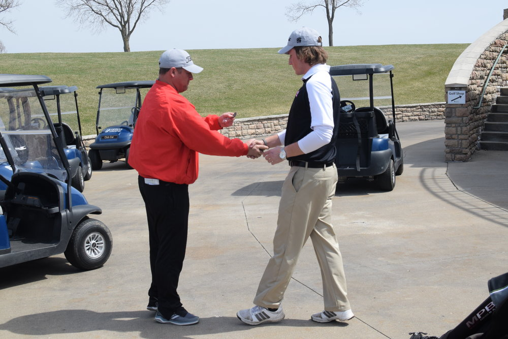BRYCE MERENESS/Citizen photo Trojans coach Zach Dorrell, left, gives a medal to Park Hill senior Davin Dorrell  after he posted a top-five finish at the  Darren Floyd memorial Golf Tournament at Tiffany Greens Golf Course on Thursday, April 5.