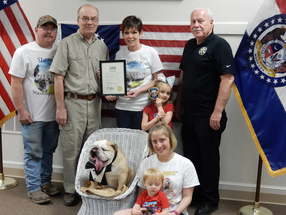 Contributed photo Stanley the Bulldog, bottom, was honored by the City of Platte City with a proclamation given on Friday, April 13. Joining him, bottom row, from left, Stanley, Megan Keating and Aedan Keating; back row, from left, Ronnie Pack, Mayor Frank Offutt, Deborah Pack, Addison Keating and Platte City Police Chief Carl Mitchell.