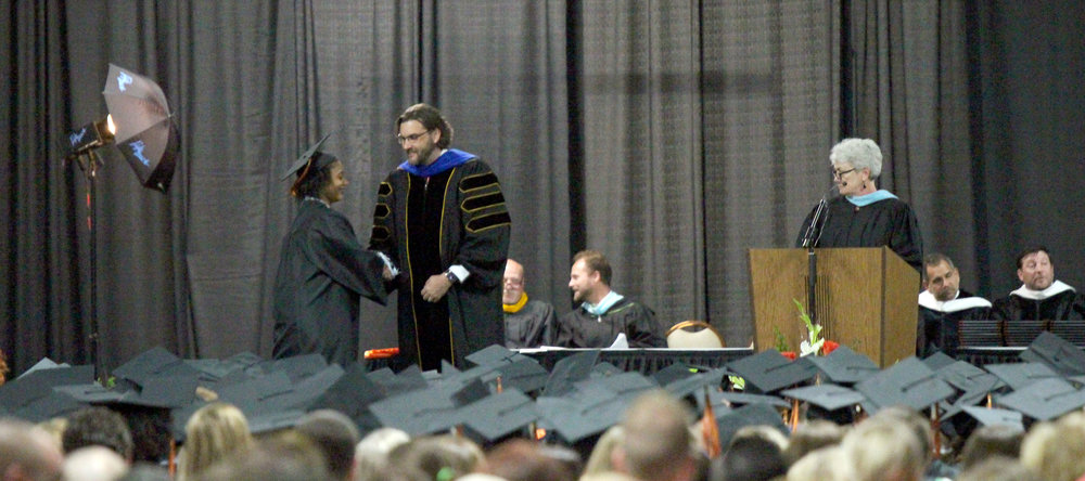 CODY THORN/Citizen photo Platte County High School principal Dr. Chad Sayre, center, shake the hand of 2018 graduate Dasia Banks, while school board president Sharon Sherwood, far right, watches after announcing Banks' name during the commencement ceremony on Sunday, May 20, at the KCI-Expo Center in Kansas City, Mo.