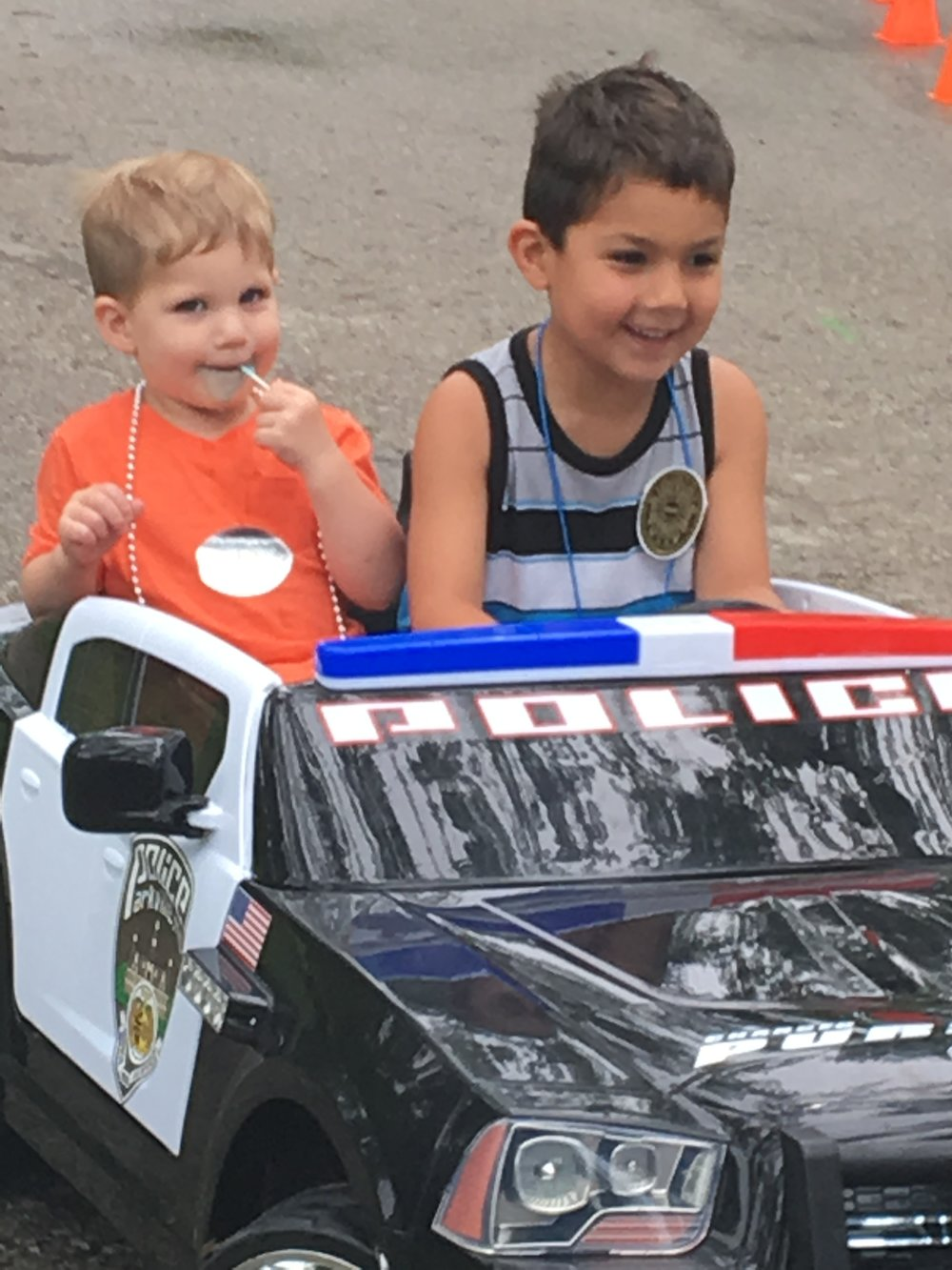JENNIFER WALLEMAN/Special to the Citizen 5-year-old Neil Williams of Kansas City drives around his brother, Clark Williams, 2, in a miniature battery-powered police car during the Northland Law Enforcement Appreciation Day.