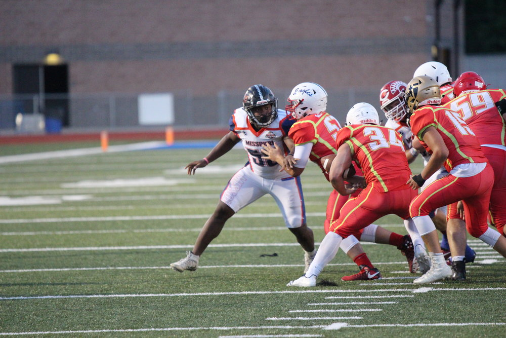 Platte County's Michael Smith, left, tries to work his way through a block by a Kansas defender during the Greater Kansas City Football Coaches Association's Missouri vs. Kansas All-Star Game held Thursday, June 14 in Leavenworth, Kan.