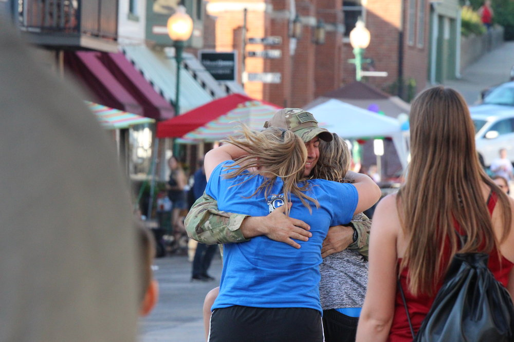 CODY THORN/Citizen photo Dearborn resident Gordon Cheadle hugs his daughters, Maddy (blue shirt) and Natalie (grey shirt) during a surprise homecoming ceremony in Weston, Missouri, on Wednesday, July 4. Cheadle had been deployed to Kuwait since February.