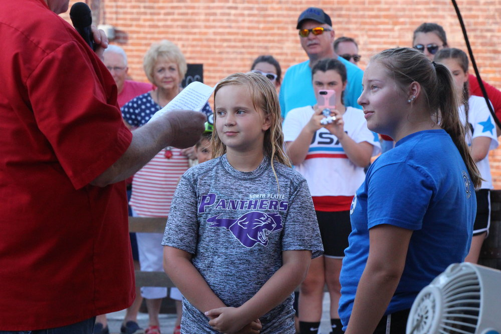 CODY THORN/Citizen photo Natalie Cheadle, 10, and Maddy Cheadle, 16, listen to Alan Lintner read a letter from their dad during a Fourth of July celebration in Weston. The girls didn't know at the time their dad was there waiting to surprise them.