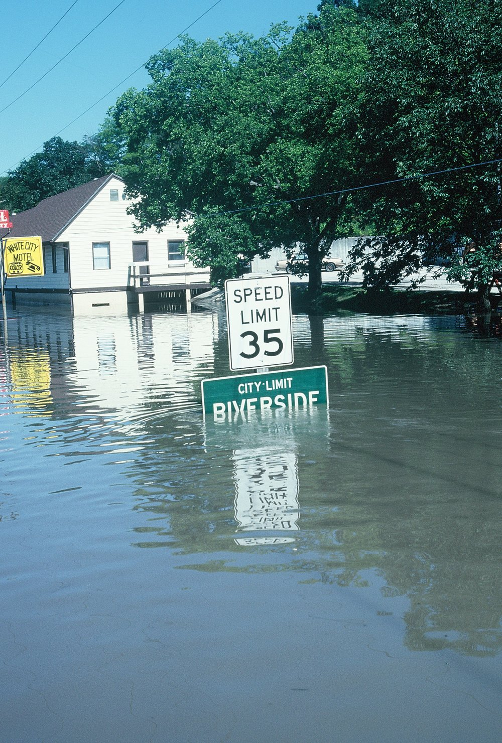 """KENNETH KIESER/ Special to the Citizen  The city limit sign into Riverside during July of 1993 shows the impact the 'Great Flood' had in the area. Towns such as Riverside, Parkville and Tracy were inundated with flood waters when the rivers left their banks. Local resident Kenneth Kieser penned a book: """"Missouri's Great Flood of 1993,"""" showcasing the photos he took during and after the flood."""