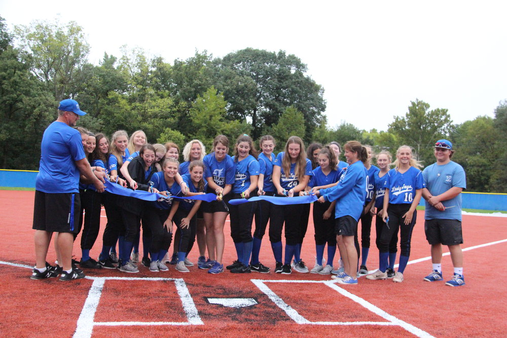 CODY THORN/Citizen photo  Members of the West Platte softball team joined coach Bailee Giger, center, in cutting the ceremonial ribbon for the new softball field on Friday, Sept. 7 at Benner Park in Weston, Mo.