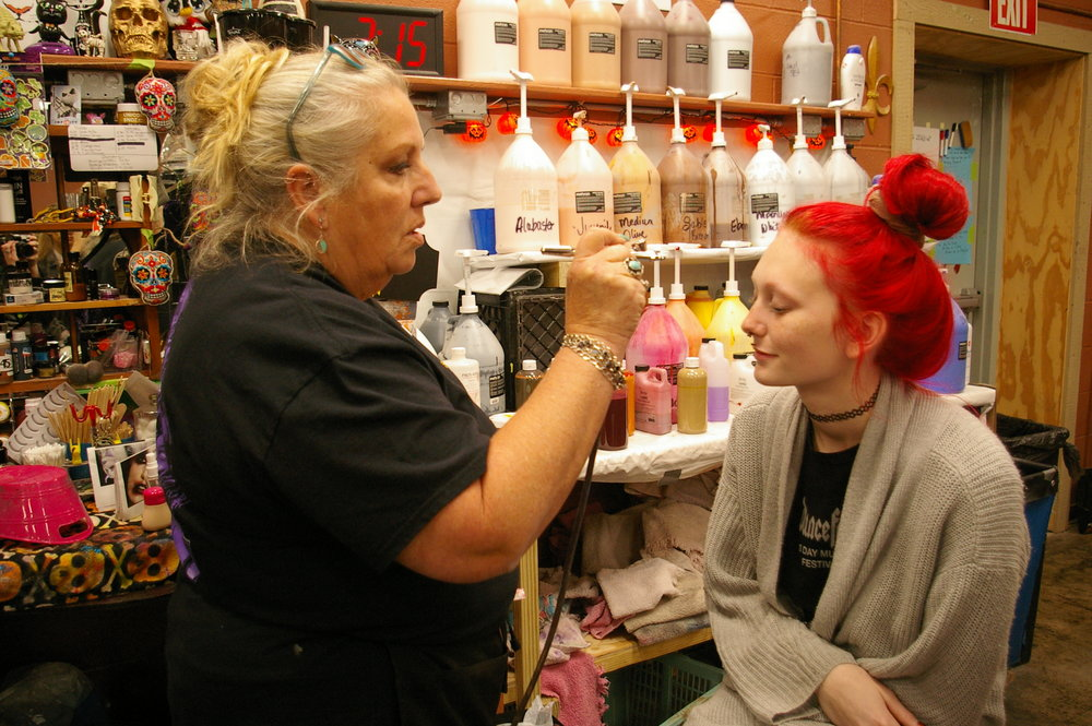 Jeanette Faubion/Citizen photo Artist Jacki Butler, left, applies makeup to actress Breck Wiley, who works as one of the minions of the Haunt Overlord, who summons up the creatures of the night at Worlds of Fun.