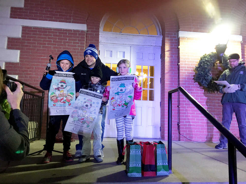 Former  Platte County Citizen  editor/publisher Ross Martin, center, poses for a photo with the coloring contest winners during the Platte City holiday lighting ceremony last year.
