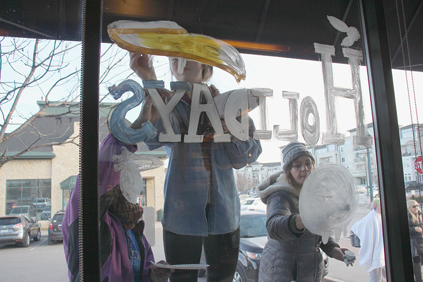 Students from Park Hill South High School's studio art class painted windows at SPIN! Pizza at the Village of Burlington Creek last week. JEANETTE FAUBION/Citizen photos