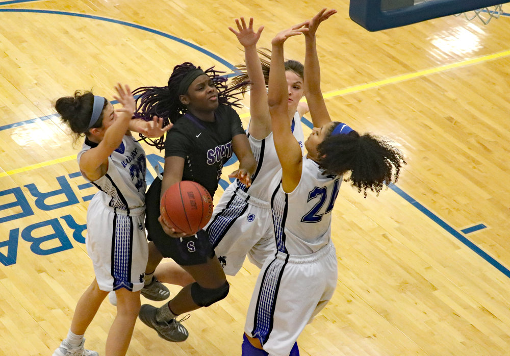 THOM HANRAHAN/Liberty-Courier Tribune Park Hill South's De'Jaria Guillory, second from left, goes up for a layup while being guarded by three Liberty defenders, including Maddie Davolt, left, and Aryonna Straws, right, on Friday, Jan. 4 at Liberty High School.