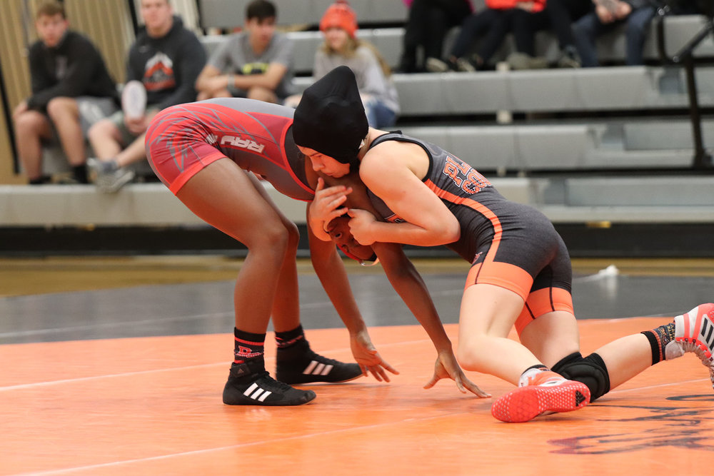 RILEY CRAWFORD/Special to the Citizen  Platte County's Avery Krahenbill, right, battles against Raytown South's Makaryla Lottie during a match on Tuesday, Dec. 18 at Platte County High School. Krahenbill picked up an 8-3 decision to help the Pirates win 9-6.