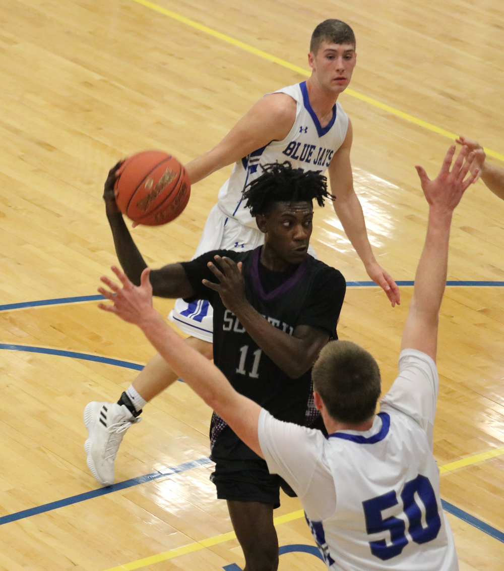 THOM HANRAHAN/Liberty-Courier Tribune  Park Hill South's Lamel Robinson, center, looks to pass while being guarded by Liberty's Peyton Steenstra (50) during a game on Friday, Jan. 4 at Liberty High School.