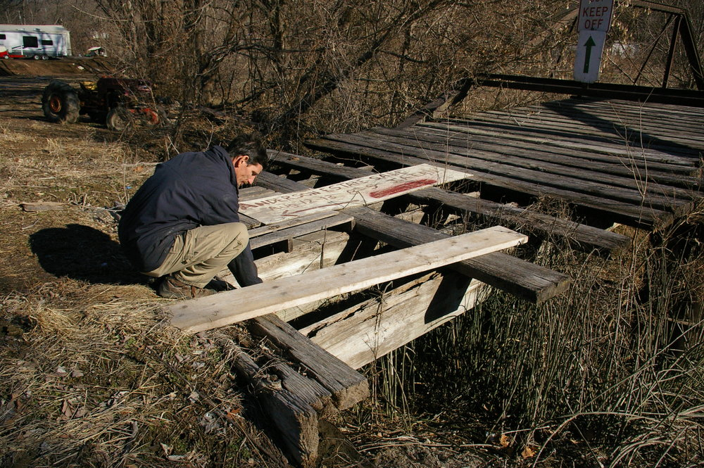 JEANETTE FAUBION/Citizen photo Village of Iatan board of trustees chair Daniel Schultz checks on boards shoring up the decking of the old Mission Creek bridge in Iatan. Schultz and the board of trustees are trying to bring back Iatan from the brink, starting with the only bridge in town, which was built in 1885.