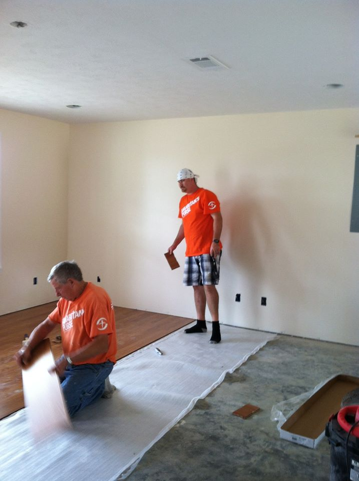 Laminate flooring being installed by Aaron, Ron and Barb