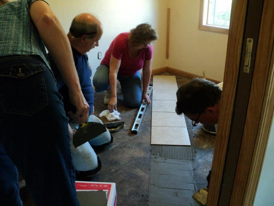 Jim, Barb and Randy start the first tiles of the project