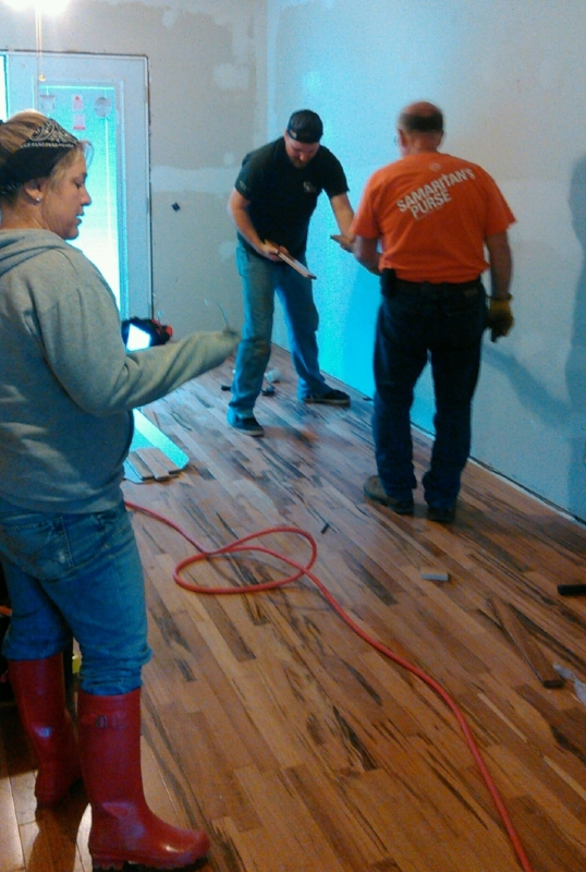 Aaron, Ben and Christina put the final pieces of flooring in place.