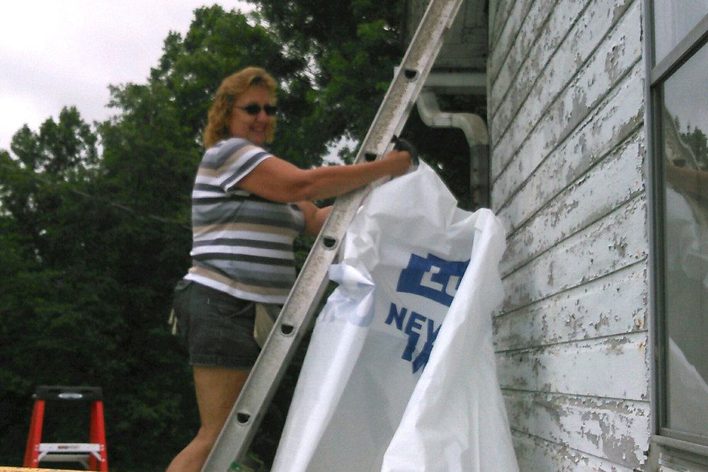 Barb helps install the house wrap.
