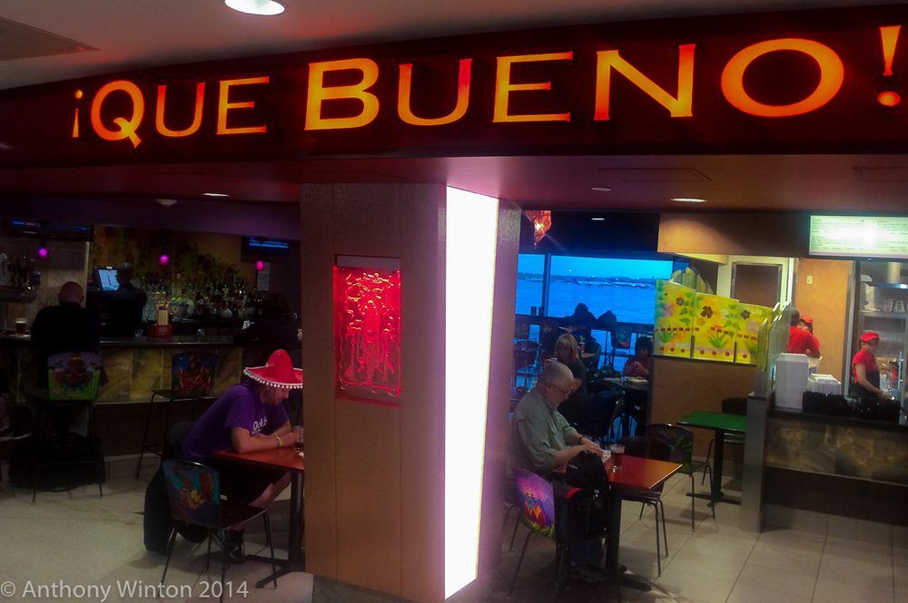 "Patrons at an airport restaurant, Denver, Colo., October, 2014. The phrase ""Que Bueno!"" means ""How good!"" © Anthony Winton 2014. All rights reserved."