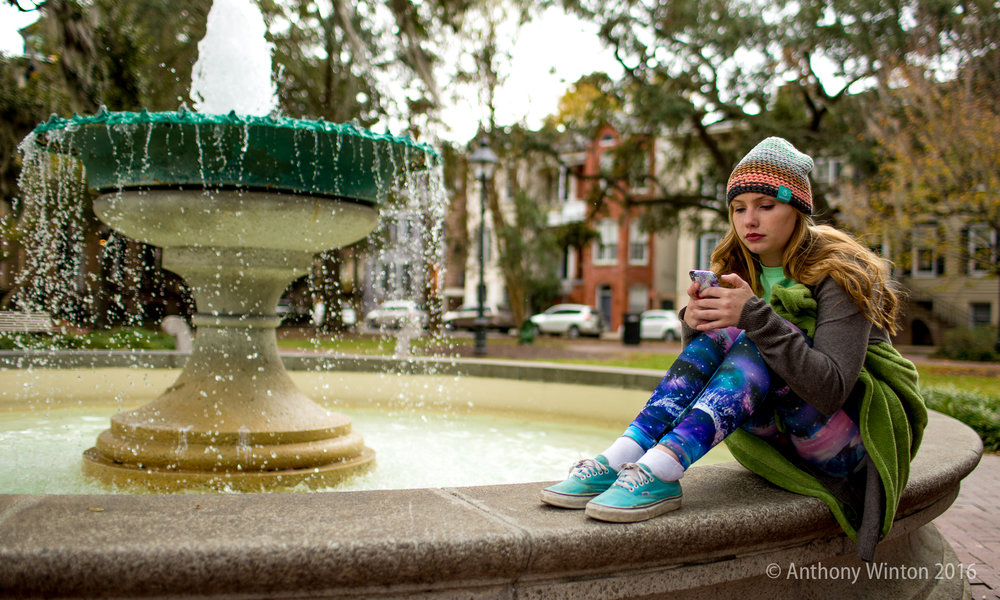 STAYING CONNECTED - A woman checks her smartphone at a park in Savannah, Ga.