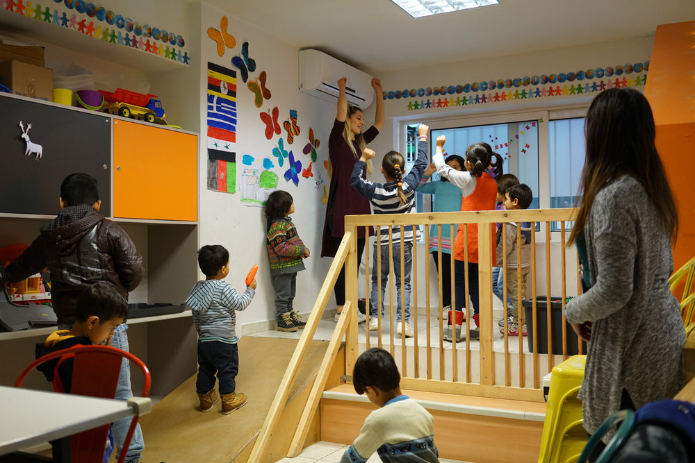 Faros staff workers play with children while their mothers drink a cup of tea nearby at the Walk-in Center.