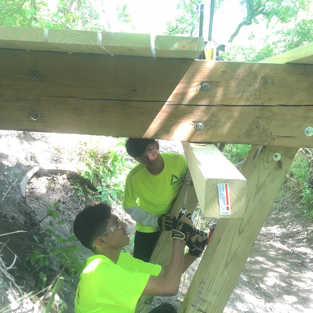 Installing tread and adding support cables to a bridge at River Legacy Park, Green Team Conservation Corps 2018.