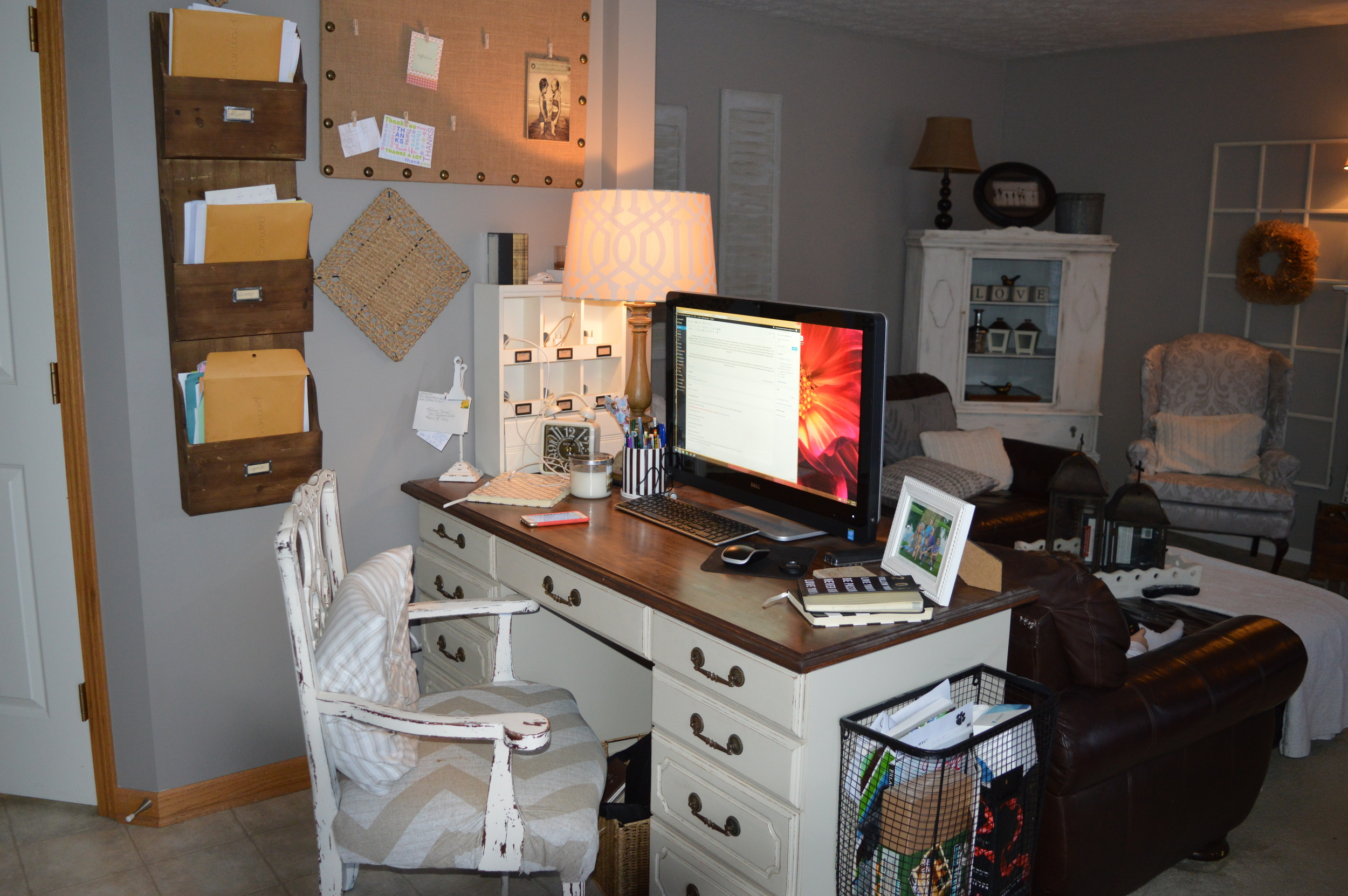 This is our office...in what should be the breakfast nook.  The overhead light is off center and this is a high traffic area for us, so I stuck a desk here and TA DA!  Office!  It's never organized and that basket on the end is forever overflowing with weird junk, it's my visible junk drawer!
